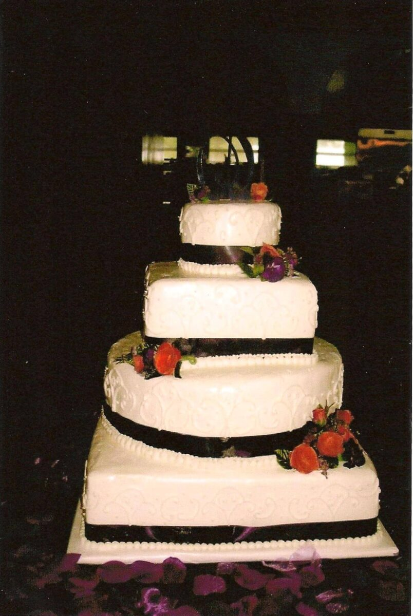 White Frosted 4 Tier Wedding Cake with Black Ribbon and Orange Flowers