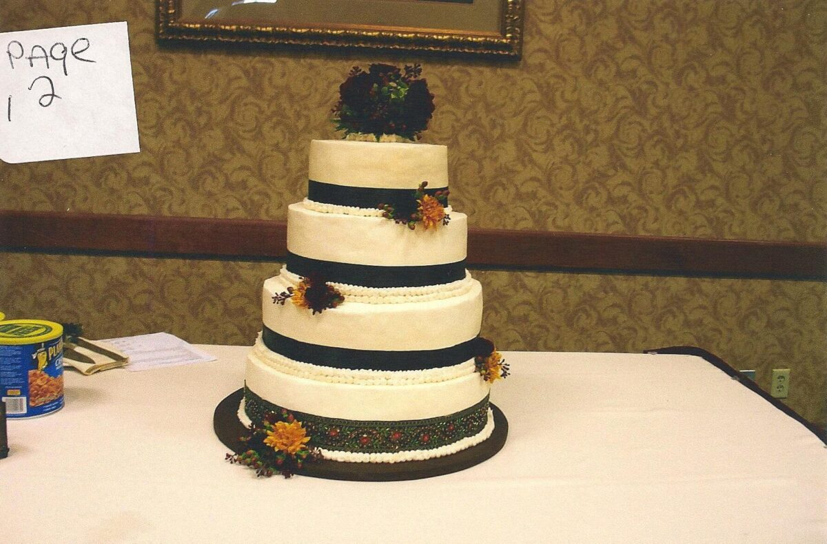 White Frosted 4 Tier Wedding Cake with Black Ribbon and Yellow and Burgundy Flowers