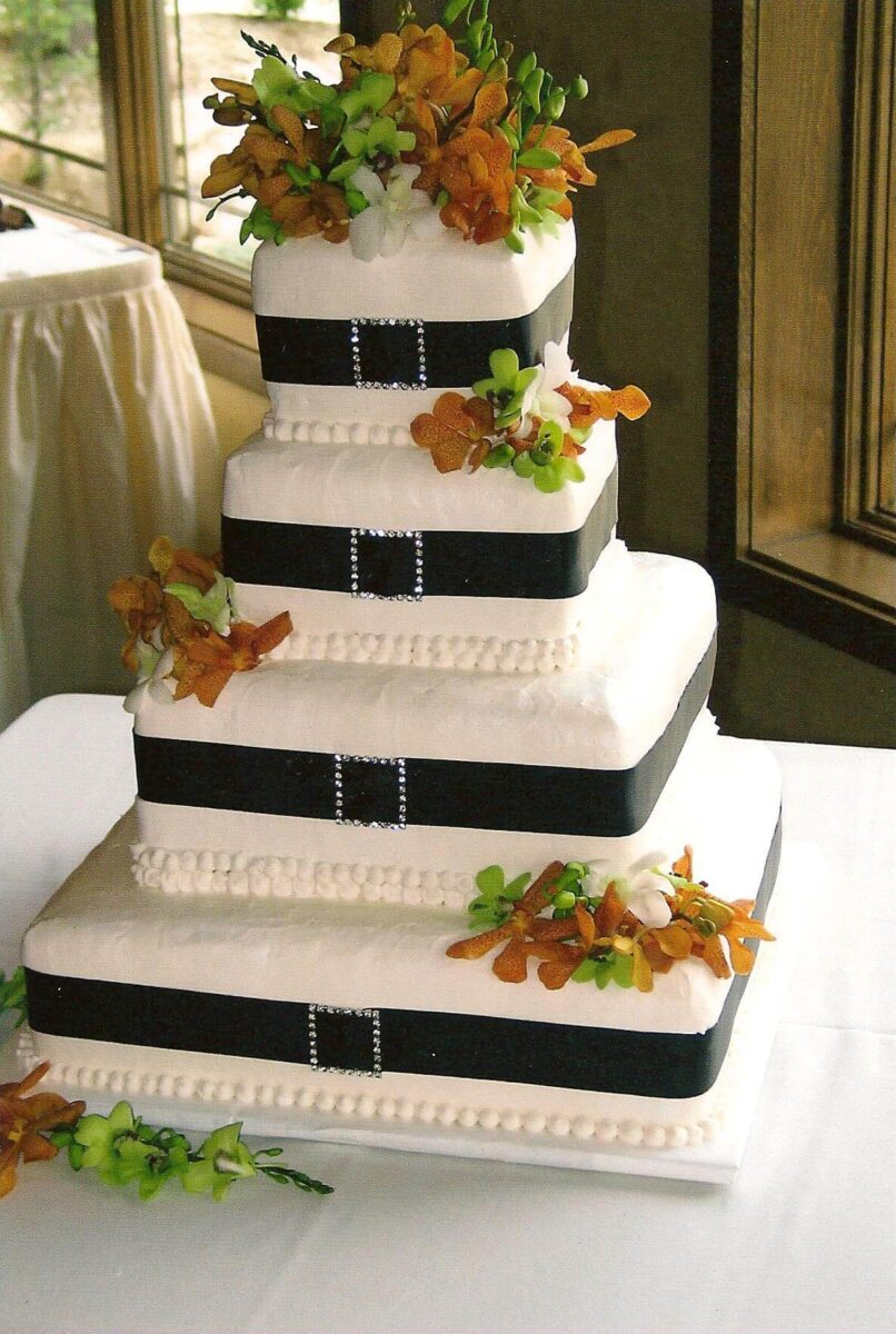 White Frosted 4 Tier Wedding Cake with Black Ribbon and Orange, White, and Green Flowers