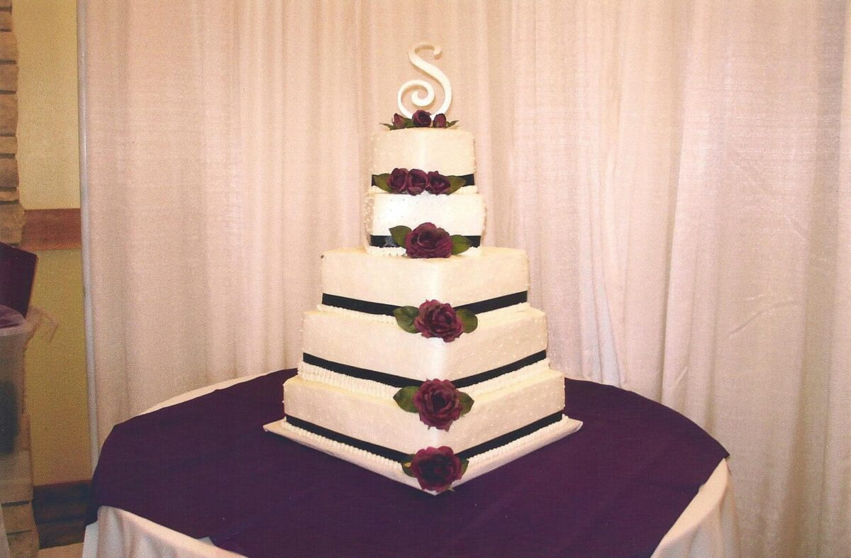 White Frosted 5 Tilted Tier Wedding Cake with Black Ribbon and Purple Roses