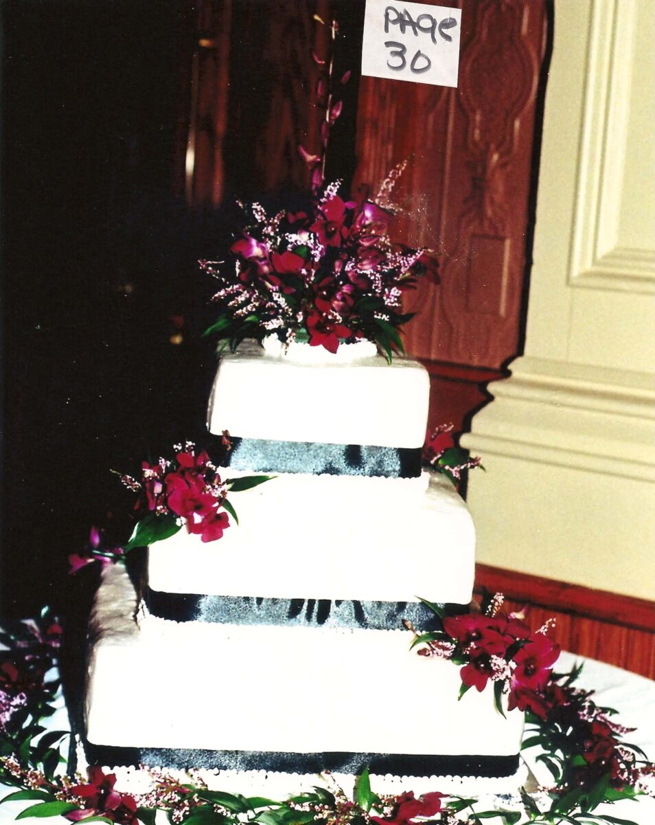 White Frosted 4 Tier Wedding Cake with Black Ribbon and Burgundy Flowers