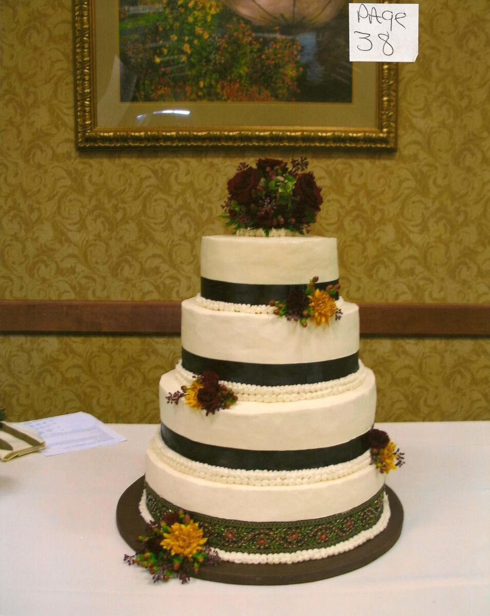 White Frosted 4 Tier Wedding Cake with Black Ribbon and Burgundy and Yellow Flowers
