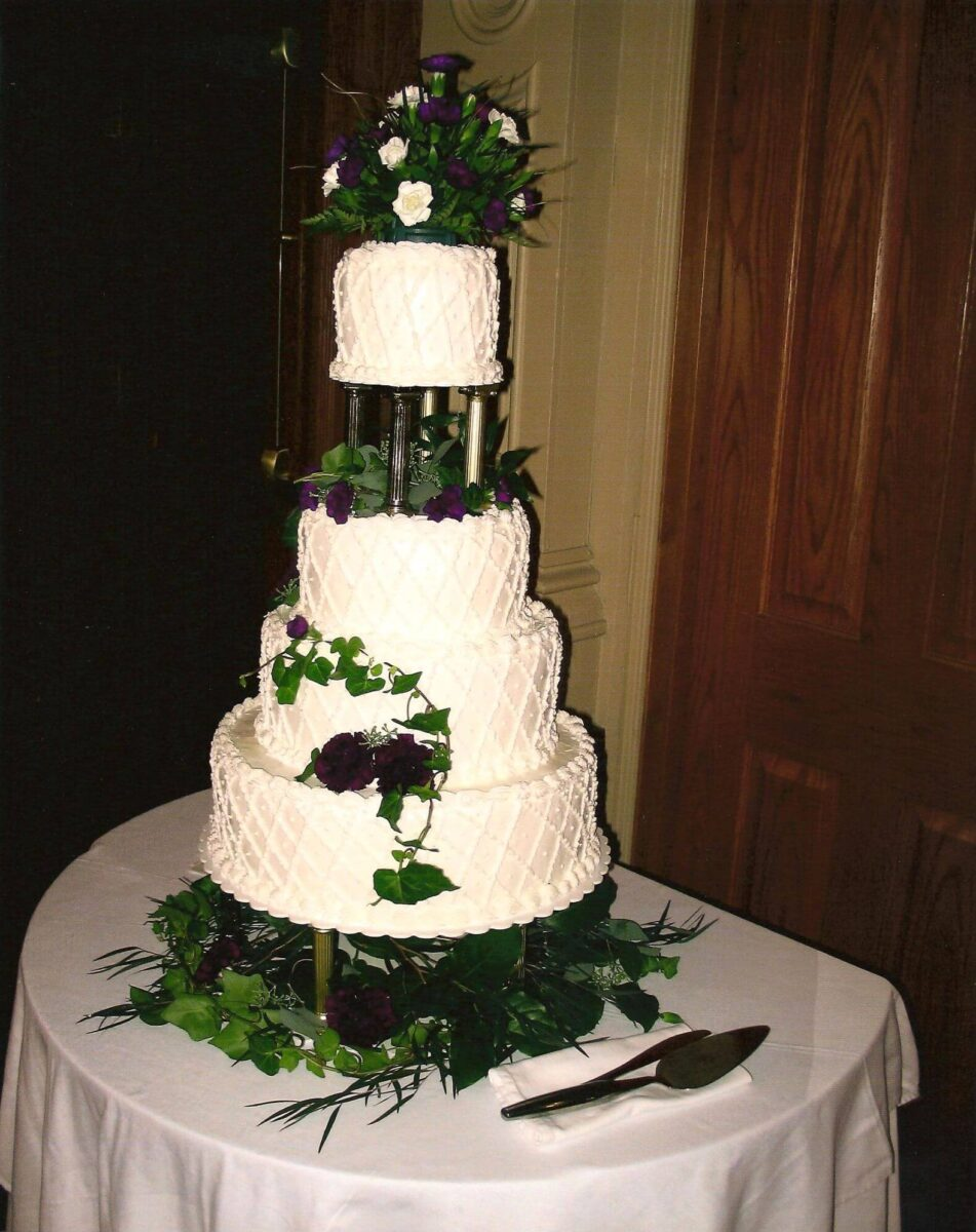 White Frosted 4 Tier Wedding Cake with Purple Flower and Greenery