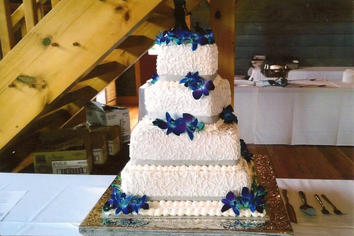 White Frosted 4 Tilted Tier Wedding Cake with Gray Ribbon and Blue Flowers