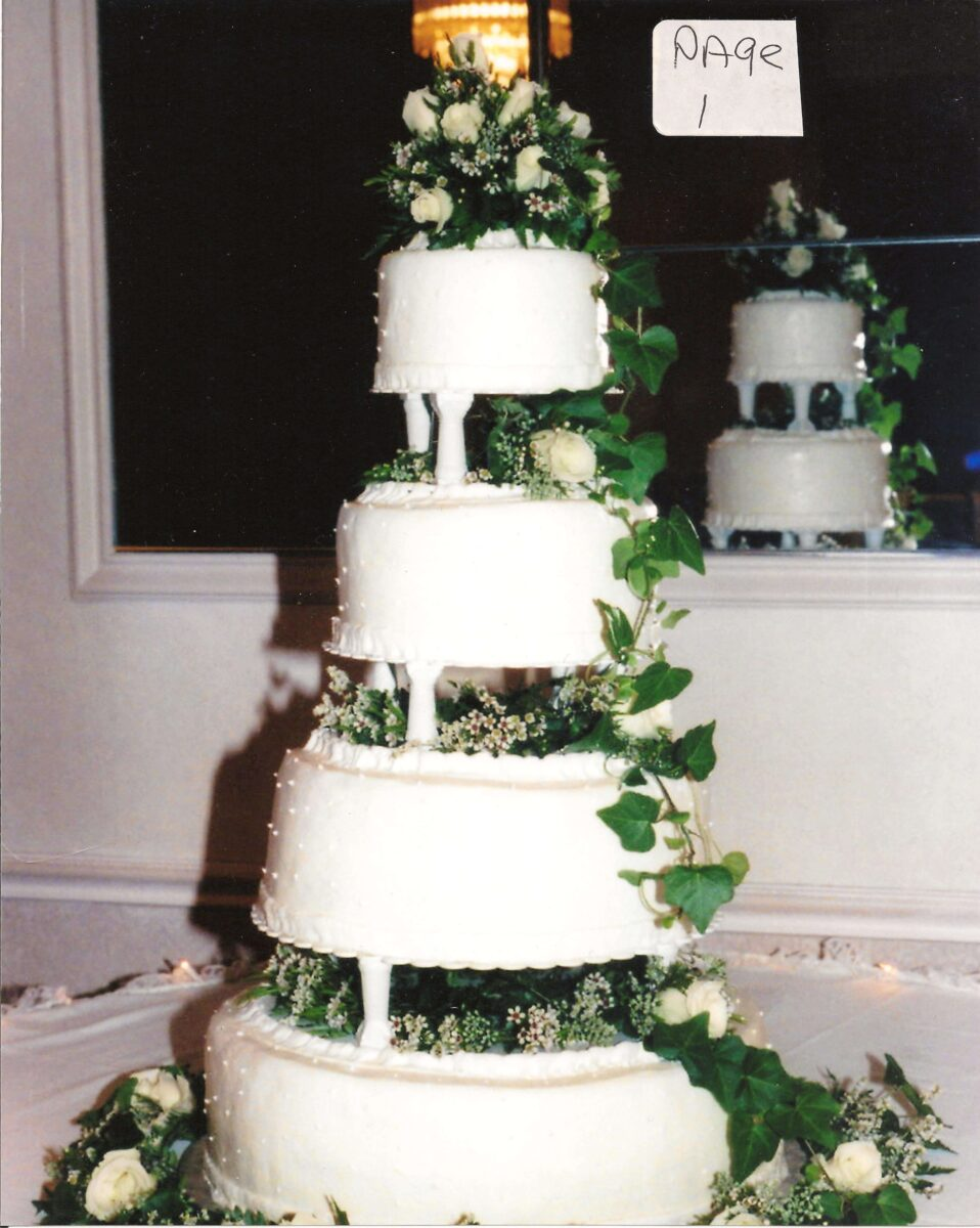 White Frosted 4 Tier Wedding Cake with White Flowers and Greenery