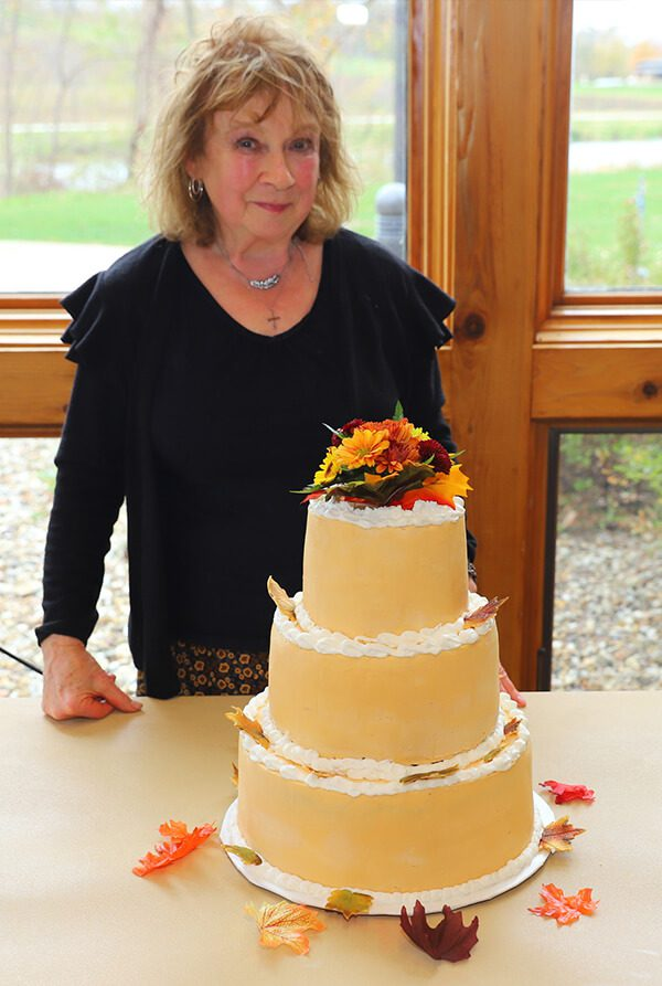 Janice with a Three Tiered Orange and White Frosted Fall Wedding Cake with Flowers and Leaves