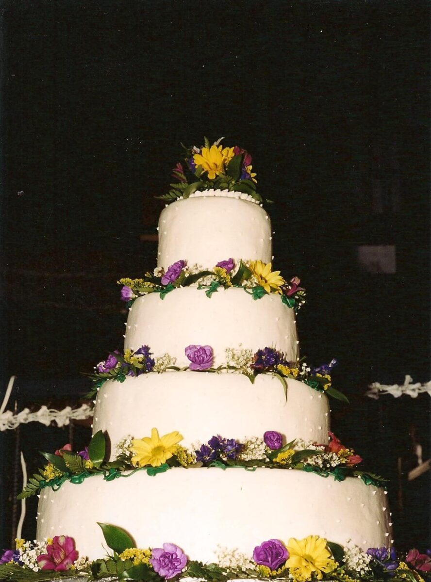 White Frosted 4 Tier Wedding Cake with Yellow, Purple, and Pink Flowers