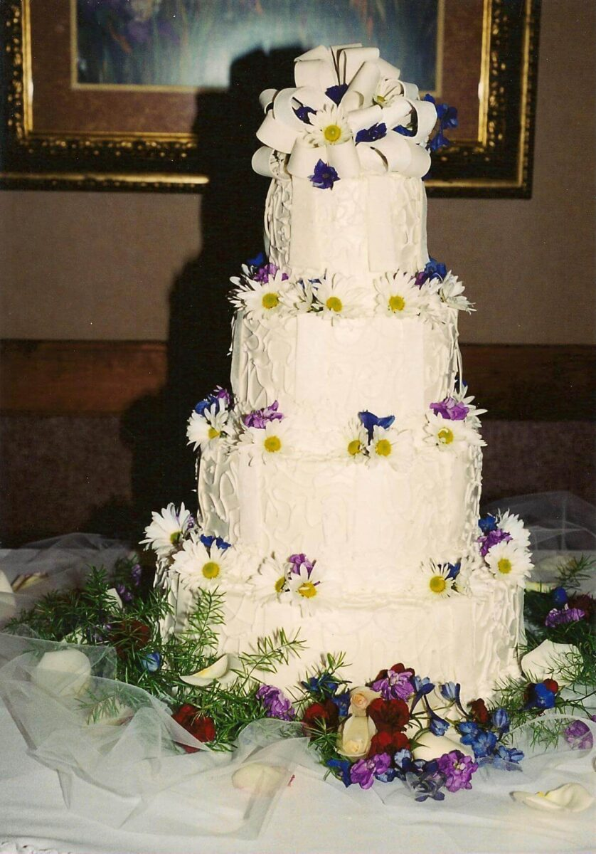 hite Frosted 4 Tier Wedding Cake with White Ribbon and White, Blue, and Purple Flowers