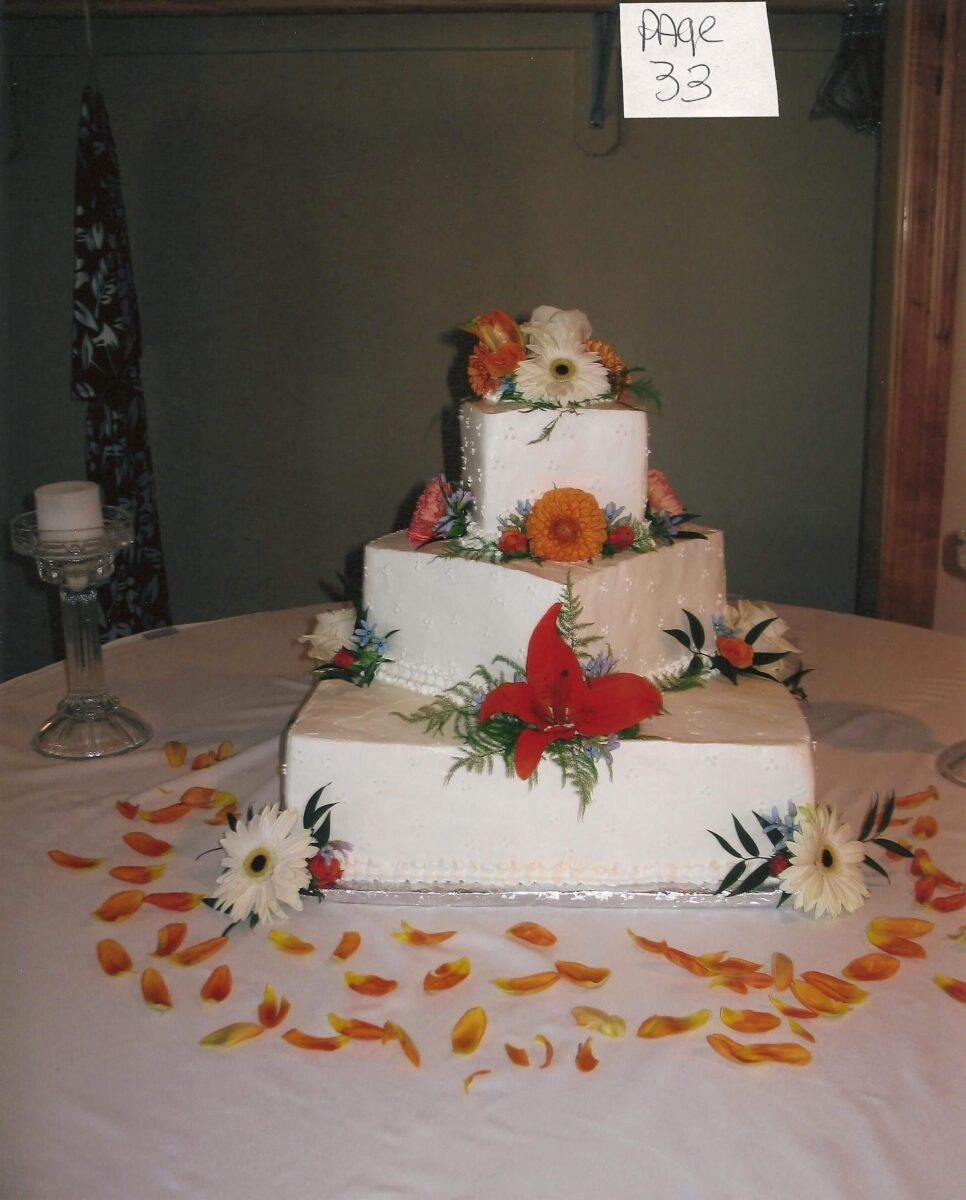 White Frosted 3 Tilted Tier Wedding Cake with Orange and White Flowers