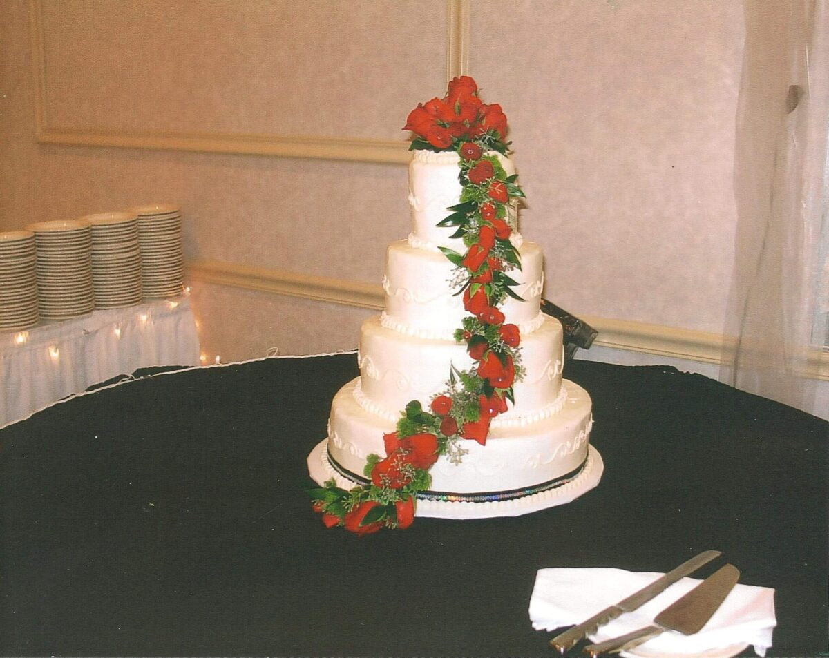 White Frosted 4 Tier Wedding Cake with Black Ribbon and Red Flowers