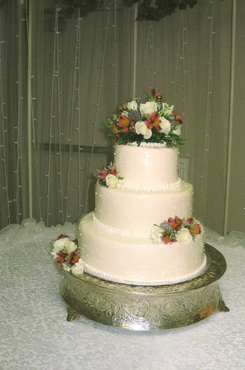 White Frosted 3 Tier Wedding Cake with Orange and White Flowers