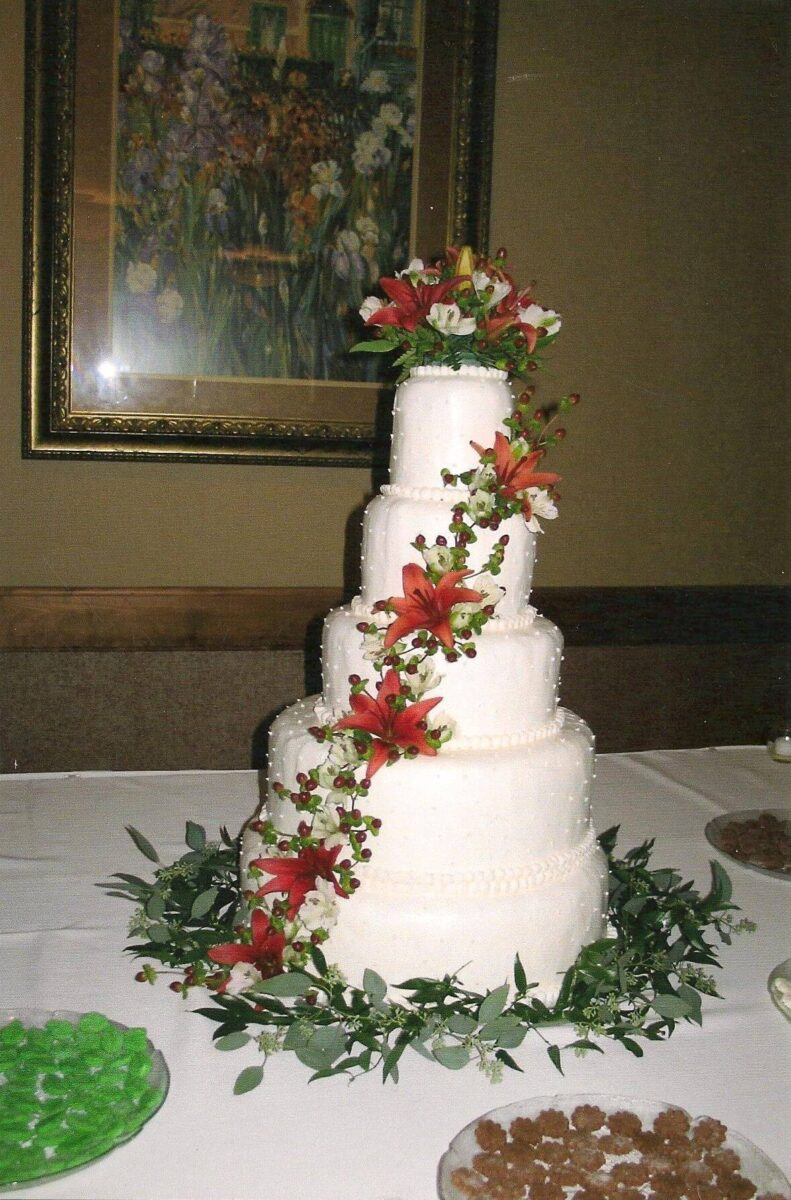 White Frosted 5 Tier Wedding Cake with Orange Lillies, white flowers and greenery