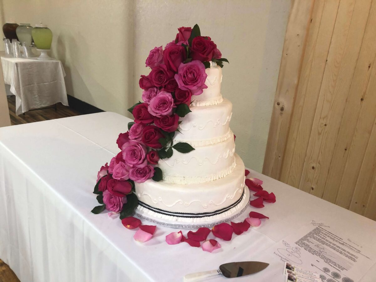White Frosted 4 Tier Wedding Cake with Black Ribbon and Red and Pink Roses