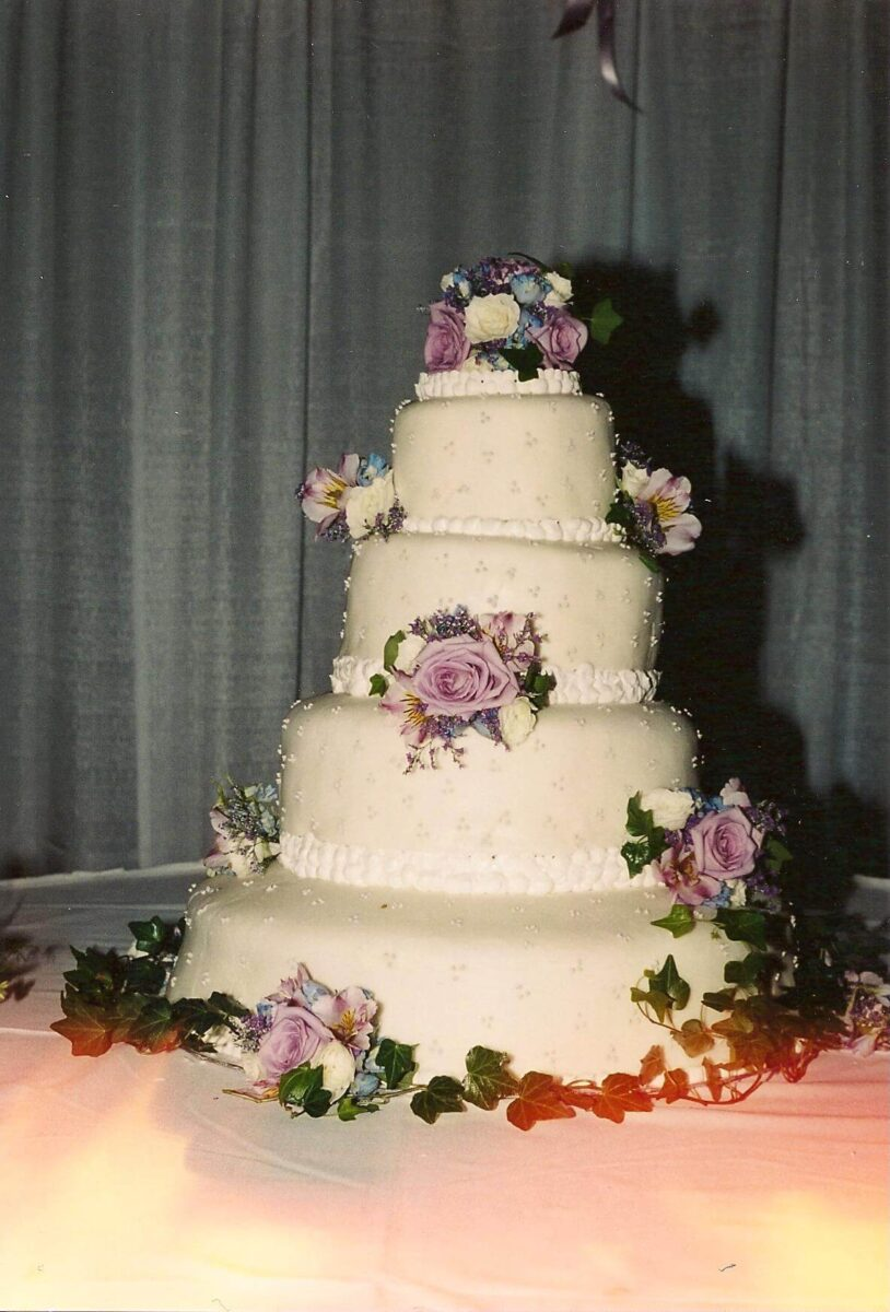 White Frosted 4 Tier Wedding Cake with Pink, White, and Blue Flowers