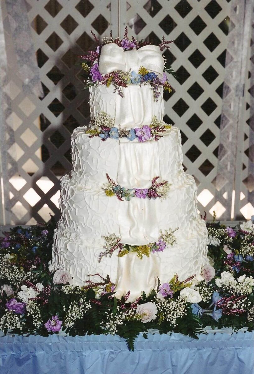 White Frosted 4 Tier Wedding Cake with White Ribbon and Pink and Blue Flowers