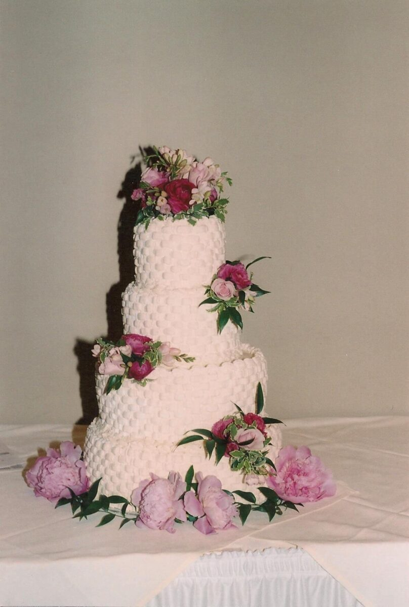 White Frosted 4 Tier Wedding Cake with Pink Flowers and Greenery