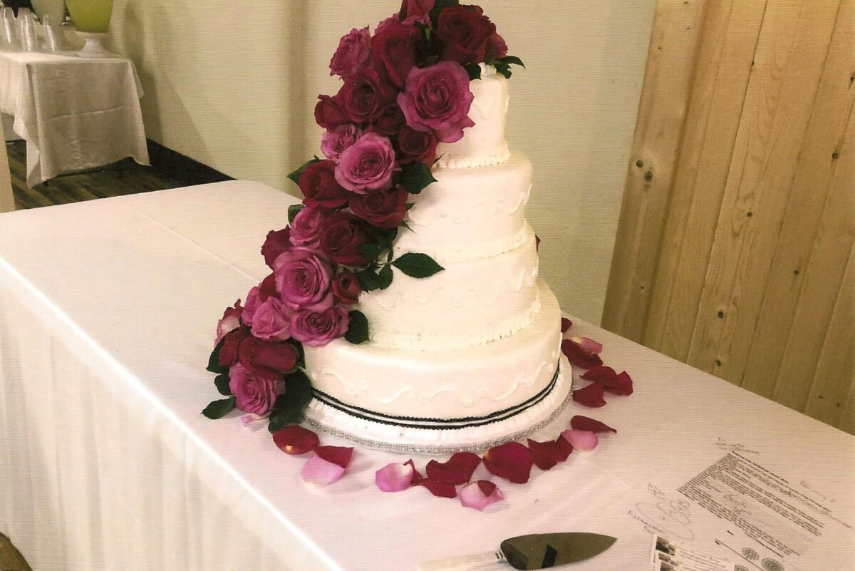 White Frosted 4 Tier Wedding Cake with Black Ribbon and Roses