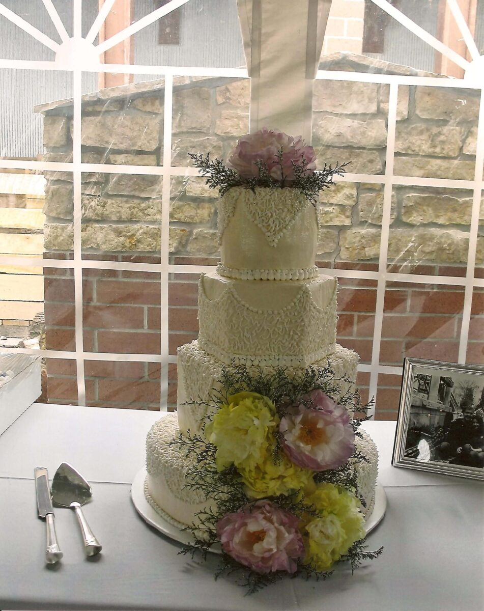 White Frosted 4 Tier Wedding Cake with Pink and Yellow Peonies