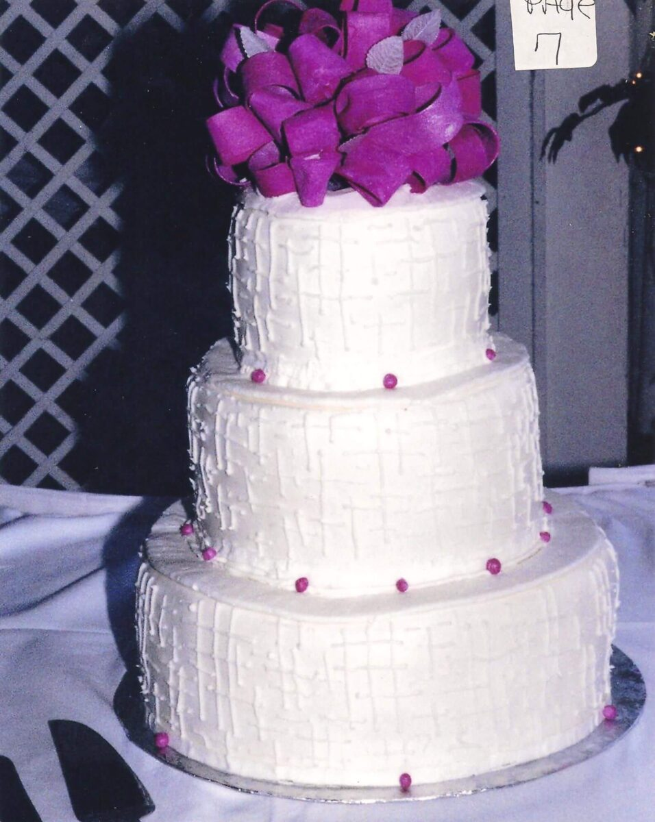 Pink and White Frosted 3 Tier Wedding Cake with Pink Ribbon