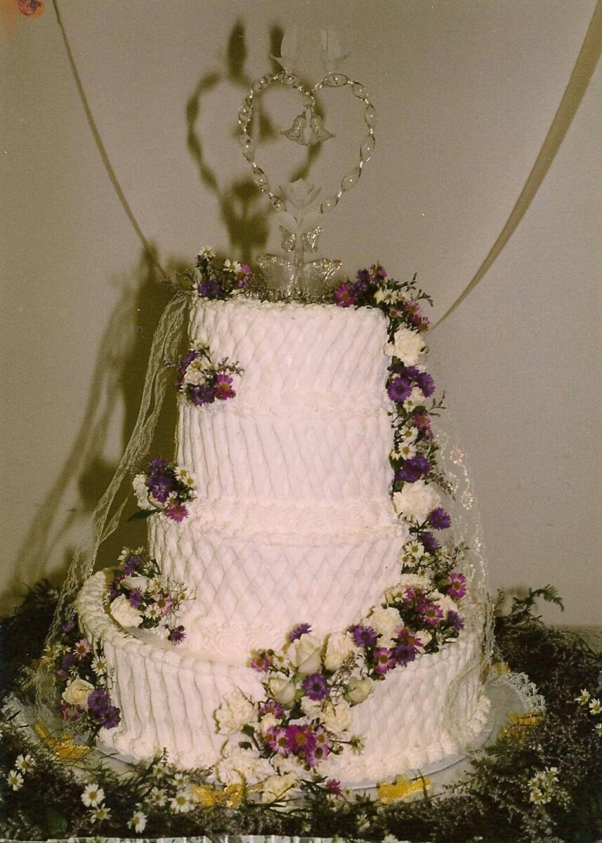 White Frosted 4 Tier Wedding Cake with White and Pink Flowers