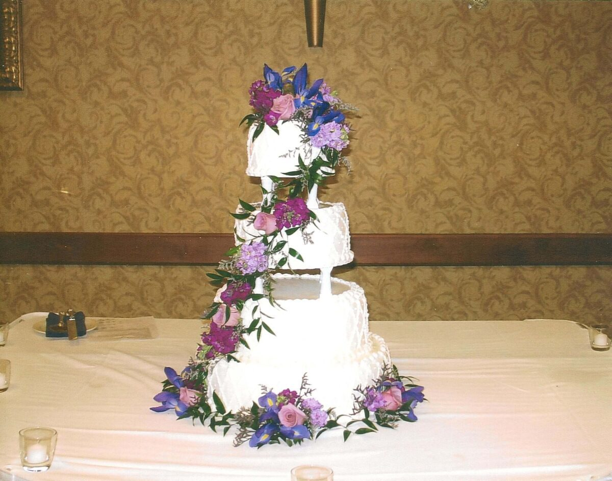 White Frosted 4 Tier Wedding Cake with Purple and Blue Flowers