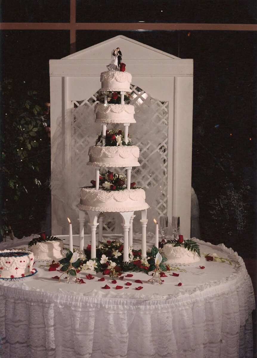 White Frosted 4 Tier Wedding Cake with Red Flowers