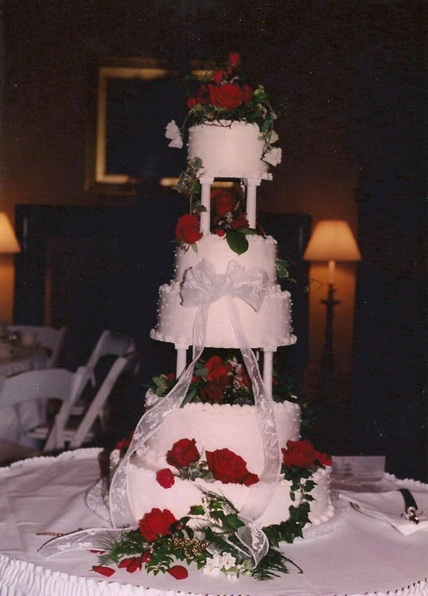 White Frosted 5 Tier Wedding Cake with White Ribbon and Red Roses