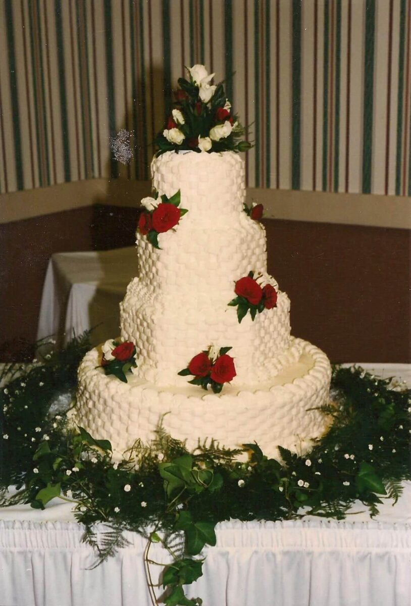 White Frosted 4 Tier Wedding Cake with Red and White Flowers