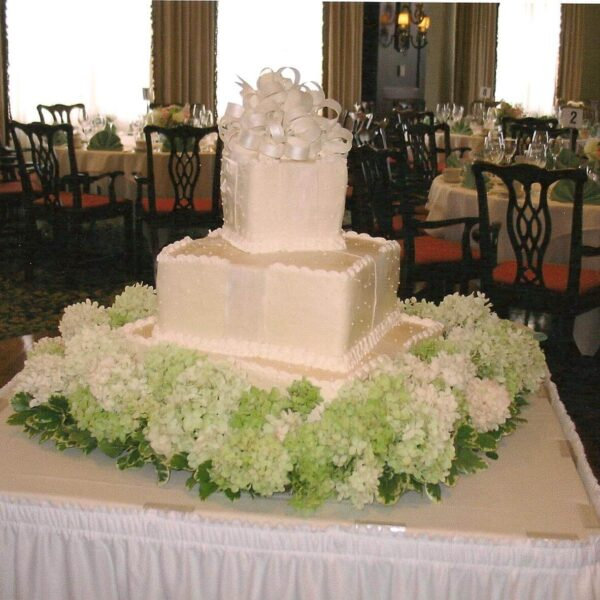 White Frosted 3 Titled Tier Wedding Cake with White Ribbon and Greenery