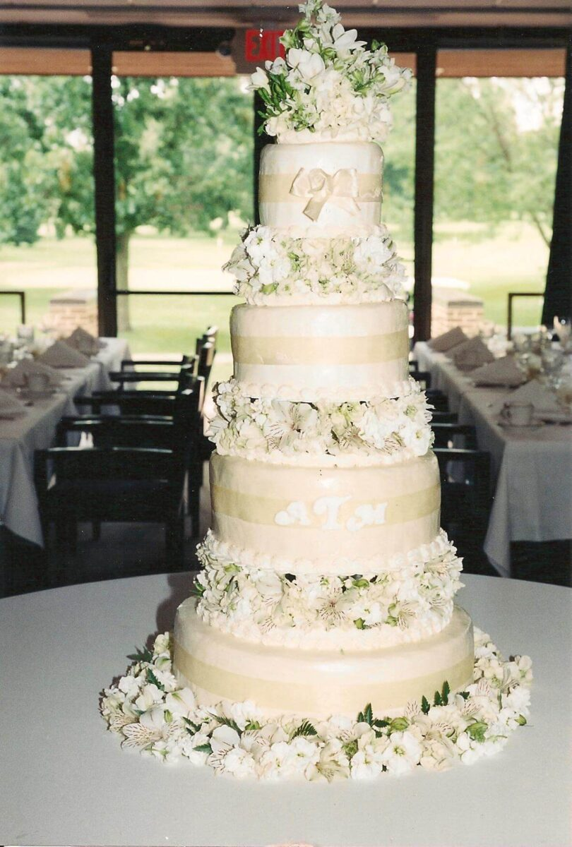 White Frosted 4 Tier Wedding Cake with White Ribbon and Flowers