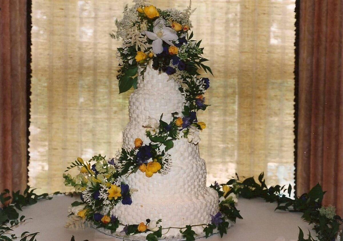 White Frosted 5 Tier Wedding Cake with Yellow, Purple, and White Flowers