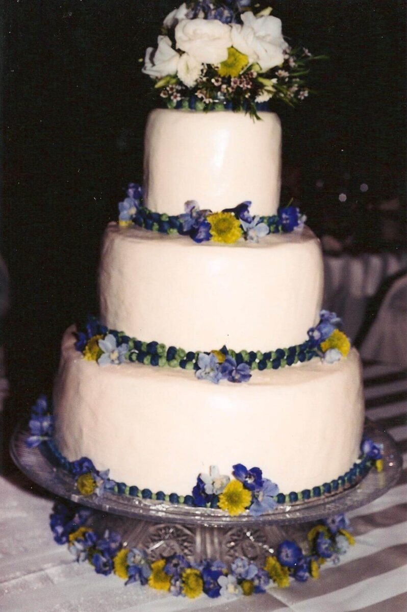 White Frosted 3 Tier Wedding Cake with Purple and Yellow Flowers