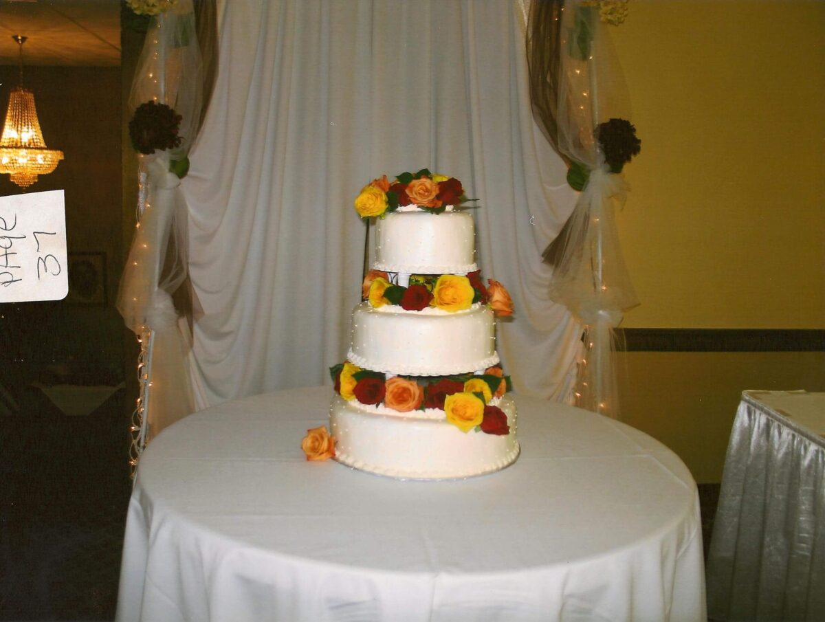 White Frosted 3 Tier Wedding Cake with Orange, Red and Yellow Flowers